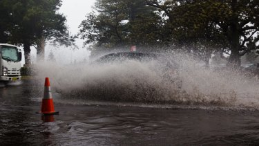 Motorists drive through the flood at New South Head Road in Rose Bay, Sydney, during the storm.