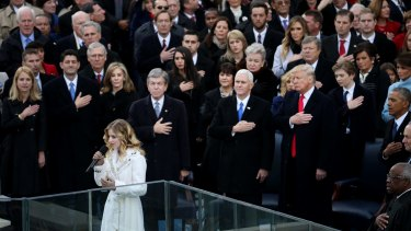 Jackie Evancho sings the US national anthem as Donald Trump looks on.