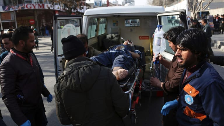 An injured man is moved by a stretcher outside a hospital following the suicide attack.