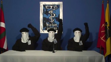 In this file image made from video provided in October, 2011, masked members of the Basque separatist group ETA raise their fists in unison following a news conference at an unknown location.