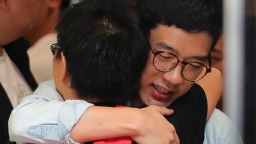 Nathan Law hugs a supporter before the ruling.