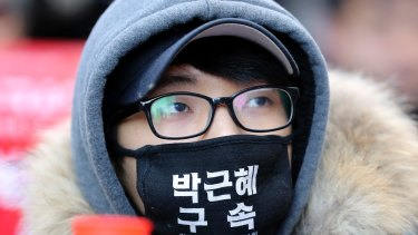 "A protester wearing a mask, attends during a rally calling for impeachment of President Park Geun-hye. The letters read ""Arrest Park Geun-hye."""
