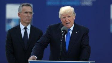 US President Donald Trump speaks as Jens Stoltenberg, secretary general of NATO, looks on.
