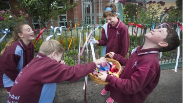 Students from the St Alipius Parish School share a funny moment while putting ribbons on the front fence of the school to acknowledge child abuse within the Catholic Church.