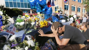 Vicente Alfaro, 15, of Irving, Texas, kneels and places his hand on a Dallas police cruiser.