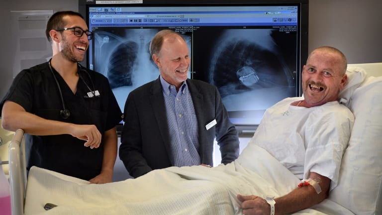 Registered nurse Michael Romero and cardiac electrophysiologist Dr Jeff Allison have put a subcutaneous implantable defibrillator (just under the skin) in Mark Heenan, 53 years old, from Doveton. This is an Australian first. You can see the device in the x-ray of Mark behind.