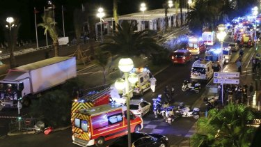 Emergency services vehicles work on the scene after a truck, left, plowed through Bastille Day revellers in the French resort city of Nice.