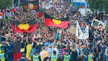 Protesters hold banners aloft as they march through the streets of the Melbourne CBD.