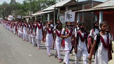 Schoolgirls wear black gags during a protest over the rape of a 16-year-old girl at Dhupguri town in the Indian state of West Bengal.