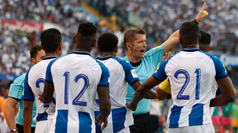 Italian referee Daniele Orsato warns off Honduras players during the first half.
