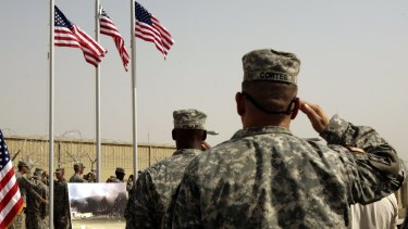 US Army soldiers saluting  American flags  at a ceremony at Camp Liberty in Baghdad  in 2008.