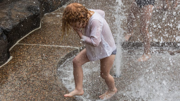 Claudia White, 4, cools off at the Wild Play Garden in Centennial Park.