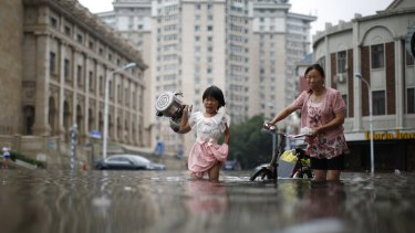 A child carries kettles through a flooded street with a woman in Tianjin, China.