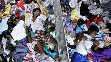 Ethnic Rohingya men take a nap on a pile of clothes donated by local residents at a temporary shelter in Langsa, Aceh province, Indonesia.