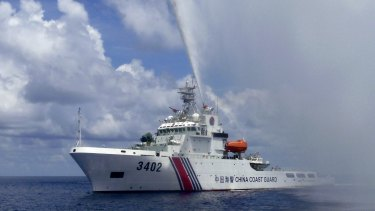 A Chinese Coast Guard boat sprays a water cannon at Filipino fishermen near Scarborough Shoal in the South China Sea last year.