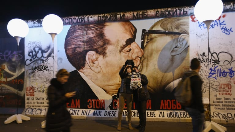 Visitors take a selfie at a mural showing former Soviet leader Leonid Brezhnev (left) kissing former East German communist leader Erich Honecker, by Russian painter Dmitri Vrubel.