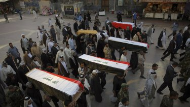 Mourners in the Iraqi city of Najaf carry the coffins of five Shiite militiamen killed on the outskirts of Tikrit during fighting with IS militants.