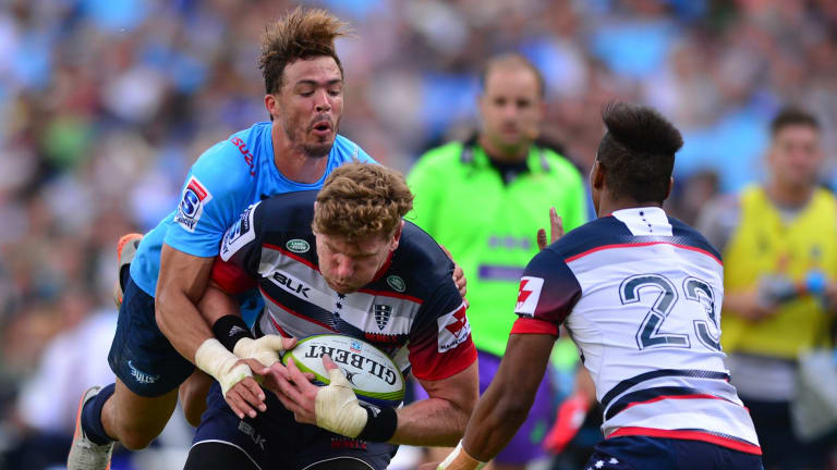 All aboard: Bjorn Basson of the Bulls launches himself at Rebels loose forward Adam Thomson in their Super Rugby match at Loftus Versfeld.