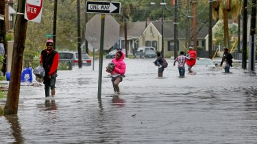 A group of people cross through high water after Hurricane Matthew caused flooding in Charleston, South Carolina.