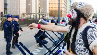 A demonstrator dressed as a clown attempts to hand a message to police during a protest outside  the European Council building in Brussels during the signing.