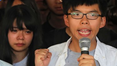 Joshua Wong, right, chants slogans as a supporter, left, reacts outside the high court before a ruling on a prosecution request for stiffer sentences in Hong Kong on Thursday.