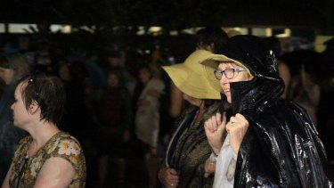 Crowds try to find shelter from the downpour at the Woodford Folk Festival.