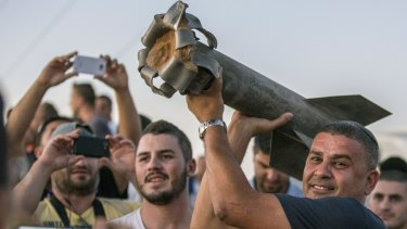 Israelis, mostly from the southern Israeli city of Sderot, show the remains of a rocket on July 13, 2014.