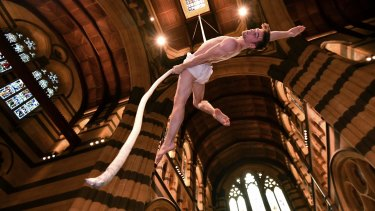 Aerial artist Tim Rutty suspended from the ceiling of St Paul's Cathedral.