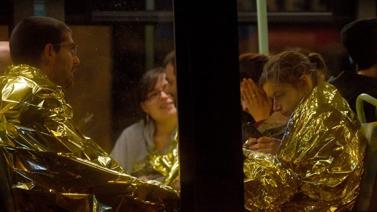 Survivors of the concert hall shooting huddle on a bus.