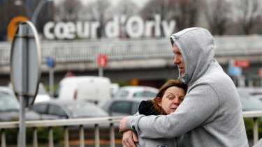 Travellers hug outside Orly airport after one of its two terminals was evacuated on Saturday.