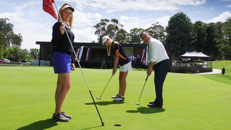 Member for Monaro and Deputy Premier of NSW, John Barilaro, tests his putting skill against sisters Chloe, (on the left holding flag) and Amber Thornton after announcing Queanbeyan GC will host the 2019 Women's NSW Open.