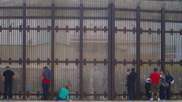 Family on the US side of the border, visit with their family members in Mexico through the border fence.