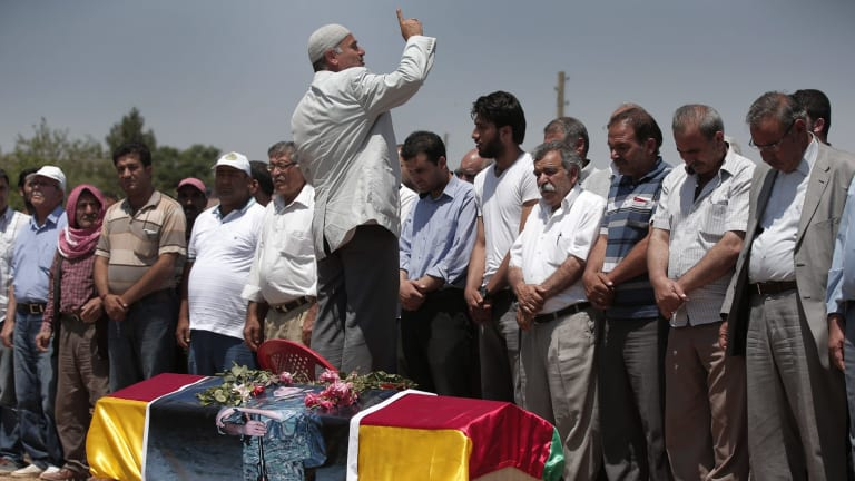 Mourners pray by the coffin of Kurdish fighter Mehmet Resat Cinar, killed in the fighting for Tal Abyad.