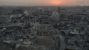 The sun sets behind destroyed buildings in the west side of Mosul in 2017.