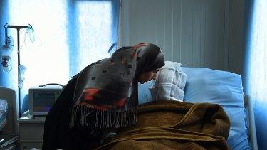 Sana Abdul Amir listens to her son Abdulrahman Abdulaaly, who has burns to 60 per cent of his body.
