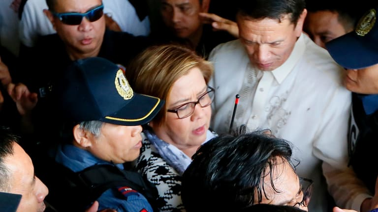 Philippine opposition Senator Leila de Lima, center, is escorted to her detention on Friday, a day after a warrant for her arrest was issued.