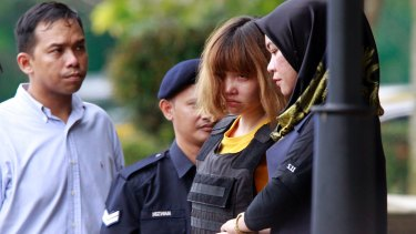 Vietnamese murder suspect Doan Thi Huong, second from right, is escorted by police officers out of court on Wednesday.