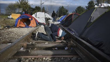 A man prays between rail tracks at the Greek-Macedonian border, near the Greek village of Idomeni on Sunday. More than 600,000 refugees and other migrants have entered Europe through Greece this year, many after making the short sea crossing from Turkey.