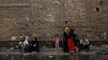 Egyptian families sit along a flooded street after their apartments were damaged in the blast.