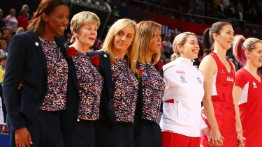 Stoic: England head coach Tracey Neville, centre, and coaching staff sing their national anthem  before the match against Scotland on Friday afternoon.