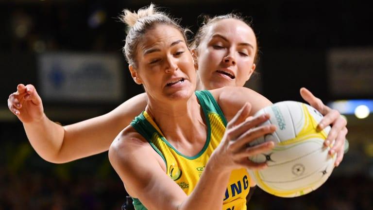 Australian goal shooter Caitlin Bassett holds off Silver Fern defender Kelly Jury in Adelaide on Wednesday night.
