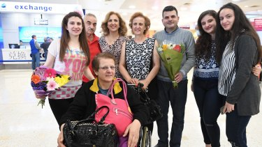 Raghida Salibi, 64, (in the wheelchair) and her two adult children, son Wessam Ozon, 38, (holding flowers) and daughter Razan Ozon, 29, are among the newest refugees to arrive in Australia.