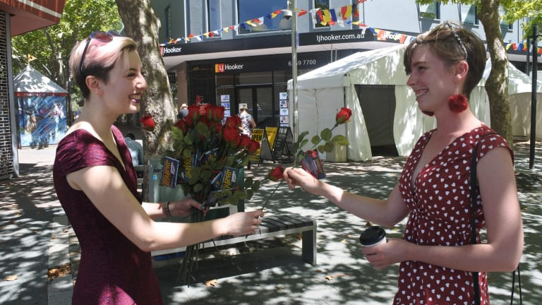 Pi Lee from Sexual Health and Family Planning gives a rose to Emily Bugden in Civic on Valentine's Day.