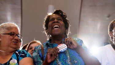 """A woman holds out her """"Nasty Woman"""" button as Hillary Clinton speaks in Sanford, Florida."""