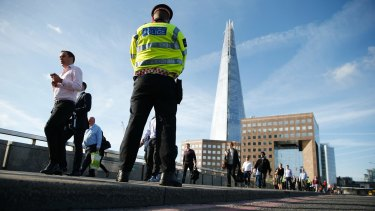 Commuters walk past a police officer on London Bridge on Monday.