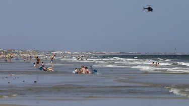 A helicopter flies close to the water as vacationers relax on the beach in Oak Island, a day after two teenagers were attacked by a shark.