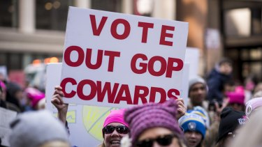 """A demonstrator holds a sign that reads """"Vote Out GOP Cowards"""" during the second annual Women's March in Chicago."""