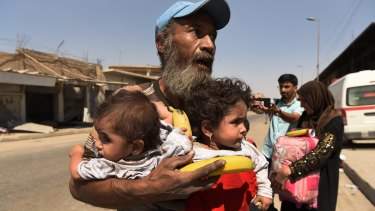 A man carries two children after being rescued from Islamic State in Mosul.