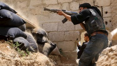 A Jaysh al-Islam (Army of Islam) rebel fighter shoots at  forces loyal to Syria's President Bashar Al-Assad on Sunday.