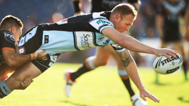 Full stretch: Luke Lewis of the Sharks reaches out to score a try.